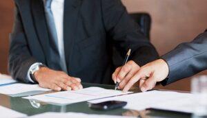 imagem de um homem de terno assinando um papel
