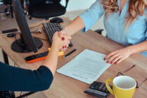 imagem aperto de mão entre duas pessoas e um contrato na mesa