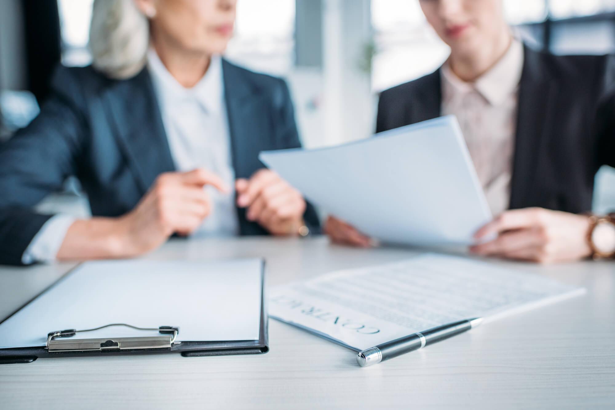 imagem de duas mulheres lendo um contrato