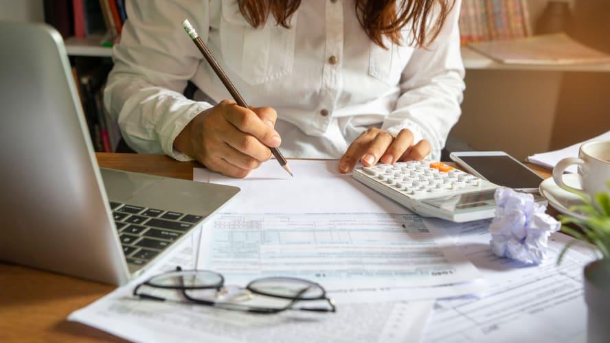 imagem de uma mulher com uma calculadora fazendo anotações