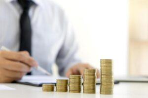 imagem de uma pilha de moedas em cima da mesa com um homem ao fundo com papel e caneta na mão fazendo conferência