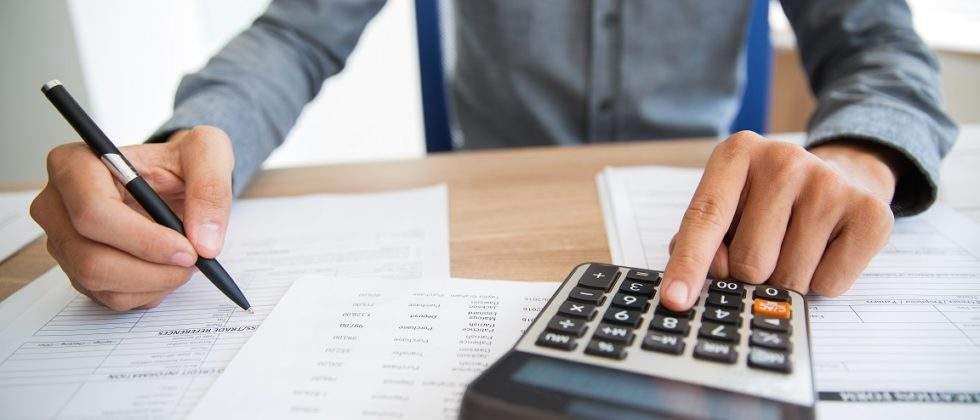 homem fazendo contas com uma calculadora
