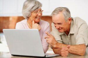 imagem de um casal da terceira idade mexendo em um notebook