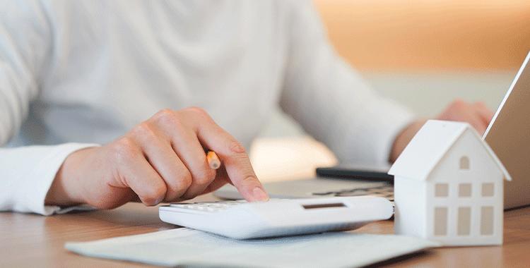 imagem mulher usando calculadora e uma casa em miniatura em cim da mesa